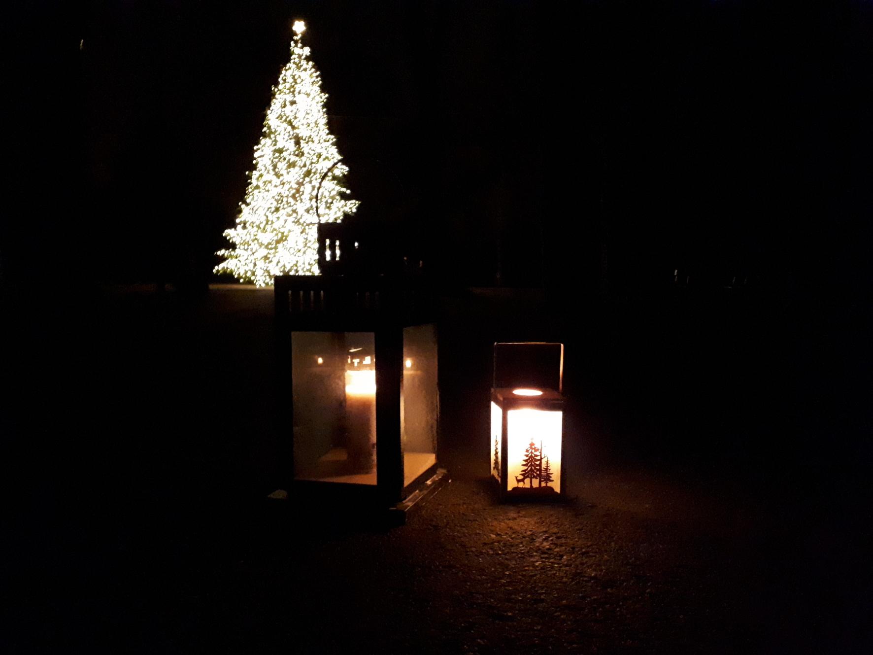 Friedenslicht vor einem beleuchteten Weihnachtsbaum