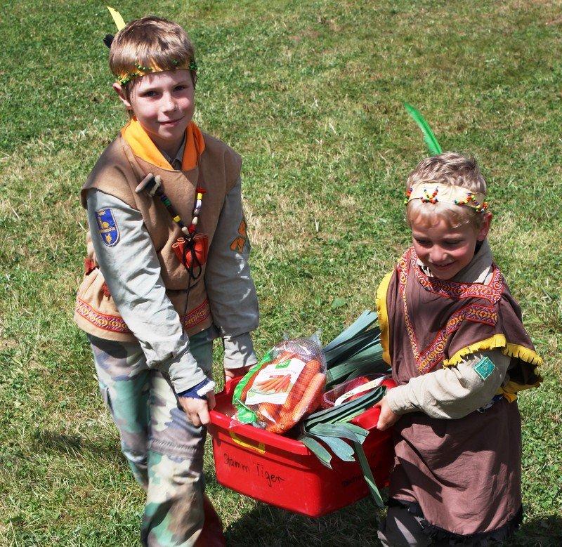 Zwei Kinder tragen einen Korb mit Essen